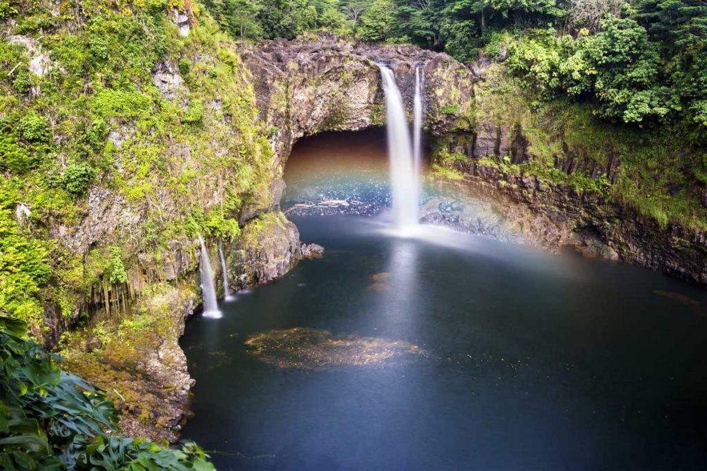 Rainbow into pool of water in Hawaii